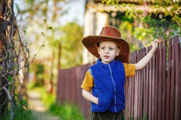 Retrato de un niño de pie con un gran sombrero en la valla de madera en el campo