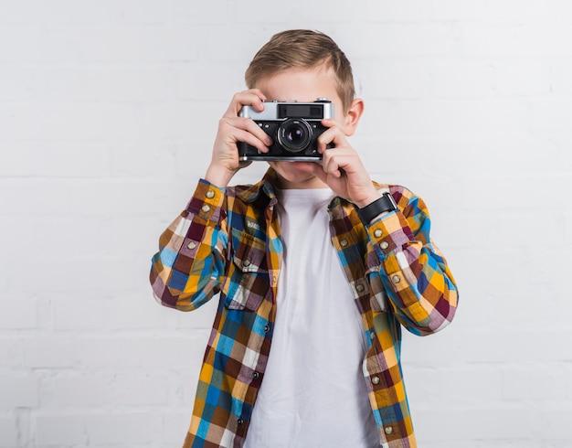 Retrato de un niño que toma una foto de una vieja cámara vintage contra una pared de ladrillo blanco