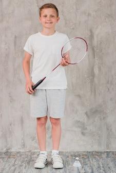 Retrato de un niño con una raqueta y un volante frente a un muro de hormigón