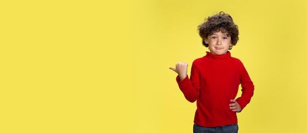 Retrato de niño rizado bastante joven en ropa roja en la expresión de la infancia de pared amarilla