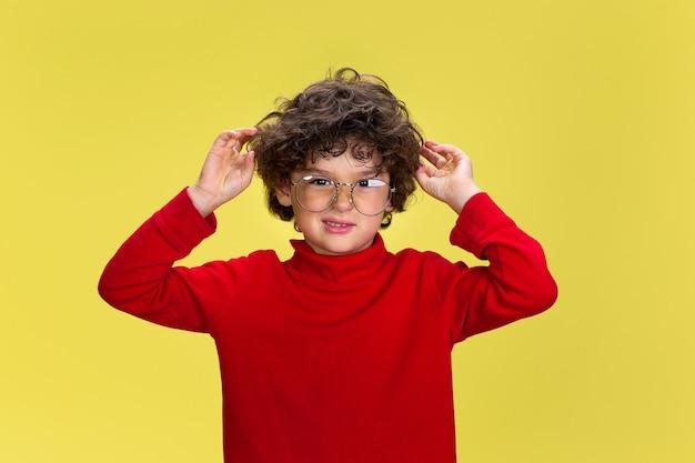 Retrato de niño rizado bastante joven en ropa roja sobre fondo amarillo de estudio. infancia, expresión, educación, concepto de diversión.