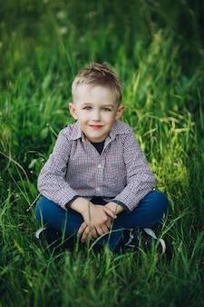 Retrato de niño rubio elegante sentado en el parque entre hierba
