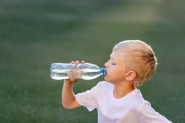 Retrato de un niño rubio con uniforme deportivo sentado en un césped verde en un campo de fútbol y bebiendo agua de una botella