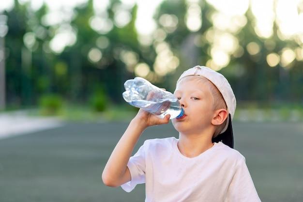 Retrato de un niño rubio con un uniforme deportivo sentado en un césped verde en un campo de fútbol y bebiendo agua de una botella