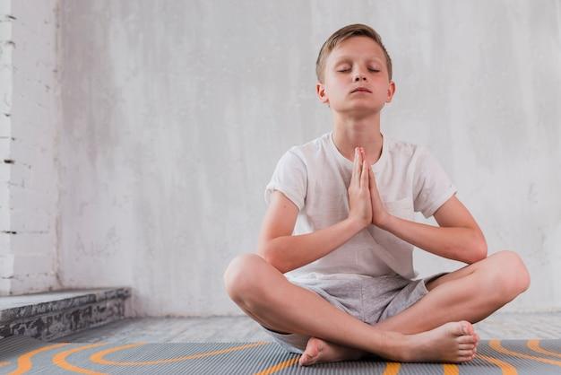 Retrato de un niño sentado en la estera de ejercicio haciendo meditación