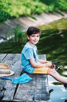 Retrato de niño sentado en el muelle de pesca en el lago