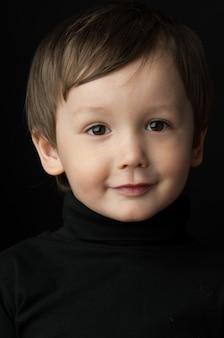 Retrato de un niño sobre un fondo oscuro
