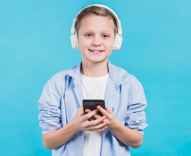 Retrato de un niño sonriente con auriculares blancos en la cabeza con teléfono inteligente en la mano contra el fondo azul