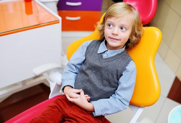 Retrato de un niño sonriente con cabello rubio rizado en el examen en una silla dental.