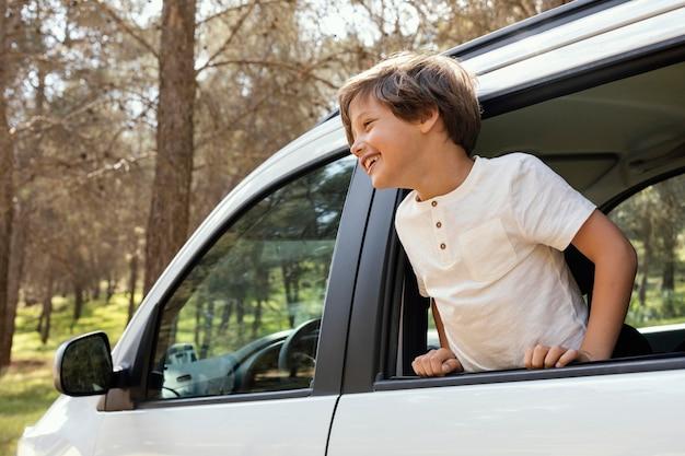 Retrato, niño sonriente, en coche