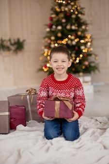 Retrato de niño sonriente feliz en suéter de punto rojo con caja de regalo de navidad cerca del árbol de navidad.