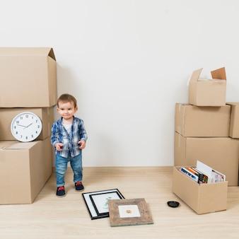Retrato de un niño sonriente parado cerca de las cajas de cartón en su nueva casa