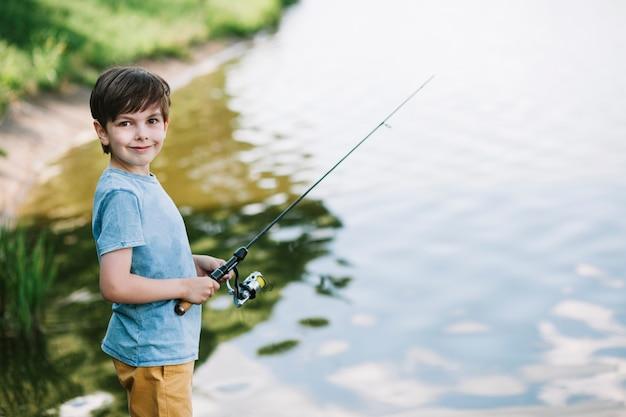 Retrato de un niño sonriente pescando en el lago