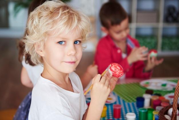 Retrato de niño sonriente pintando huevos de pascua