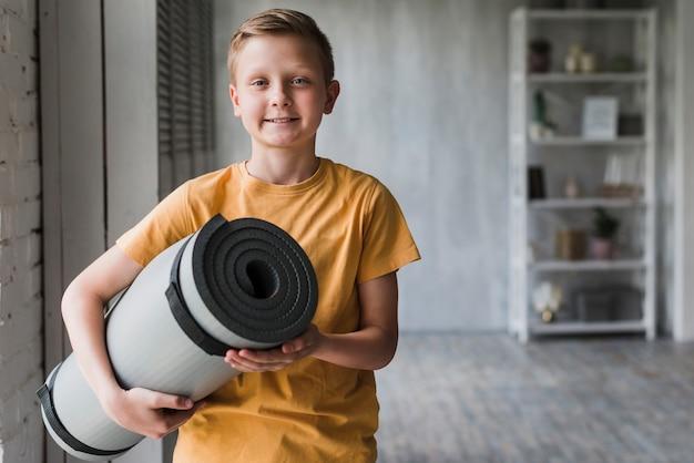 Retrato de un niño sonriente sosteniendo gris enrollada estera del ejercicio en la mano