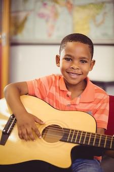 Retrato de niño sonriente tocando la guitarra en el aula
