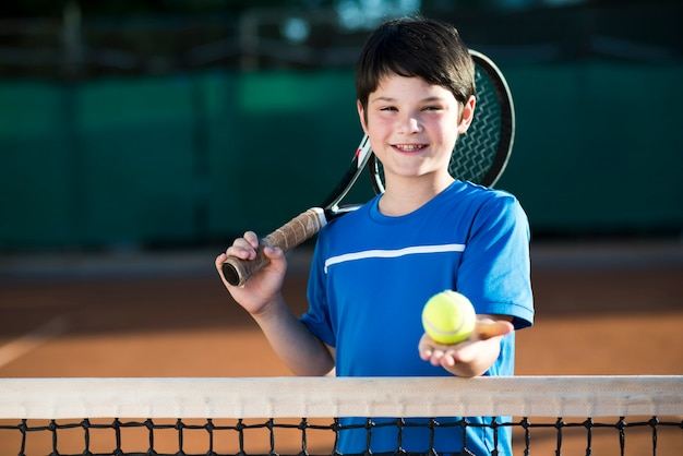 Retrato de niño sosteniendo una pelota de tenis en la mano