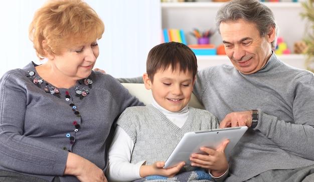 Retrato de niño con sus abuelos en casa