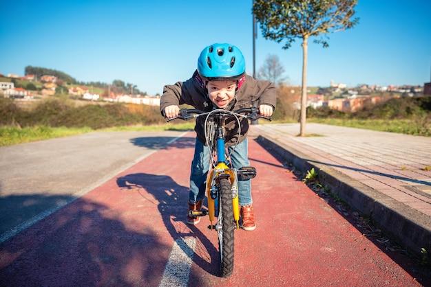 Retrato de niño travieso con gesto desafiante sobre su bicicleta lista para correr en un carril bici
