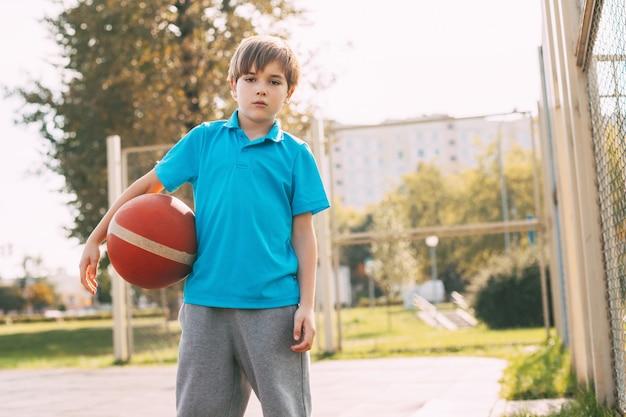 Retrato de un niño en un uniforme deportivo con una pelota de baloncesto en sus manos. deportes, educación