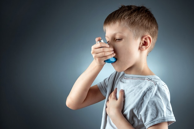 Retrato de un niño usando un inhalador para el asma para tratar enfermedades inflamatorias, falta de aliento. el concepto de tratamiento para la tos, alergias, enfermedades del tracto respiratorio.