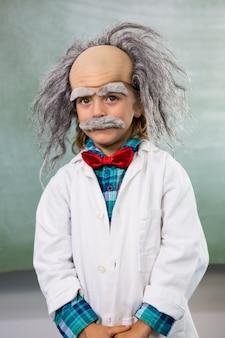 Retrato de niño vestido como científico de pie contra el tablero