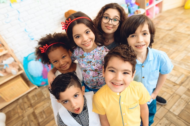 Retrato de niños alegres en sombreros de vacaciones en la fiesta de cumpleaños