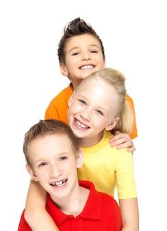 Retrato de los niños felices aislados en blanco. amigos escolares de pie juntos y mirando a la cámara