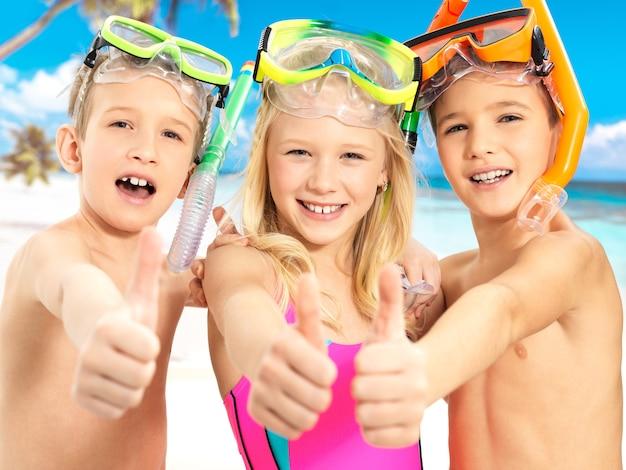 Retrato de los niños felices con gesto de pulgar hacia arriba en la playa. niños en edad escolar parados juntos en traje de baño de colores brillantes con máscara de natación en la cabeza.