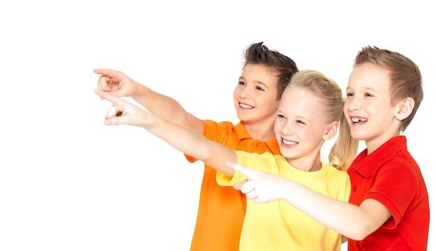 Retrato de los niños felices señalan con el dedo algo lejos - aislado en blanco