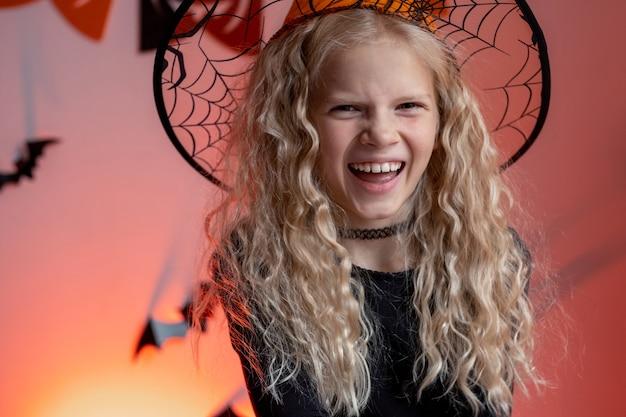 Retrato de niños de halloween niña riendo con sombrero de disfraz de bruja en casa listo para vacaciones de truco o trato