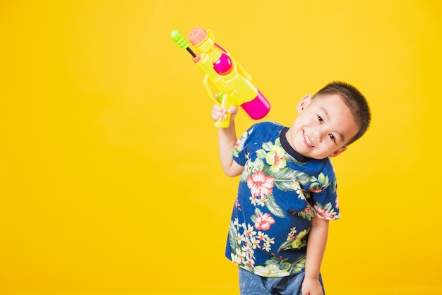 Retrato niños niño sonrisa sosteniendo pistola de agua