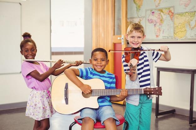 Retrato de niños sonrientes tocando la guitarra, el violín, la flauta en el aula