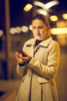 Retrato de noche tonificada de mujer joven elegante mediante teléfono móvil en la calle