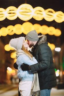 Retrato nocturno al aire libre de la joven pareja posando en la calle