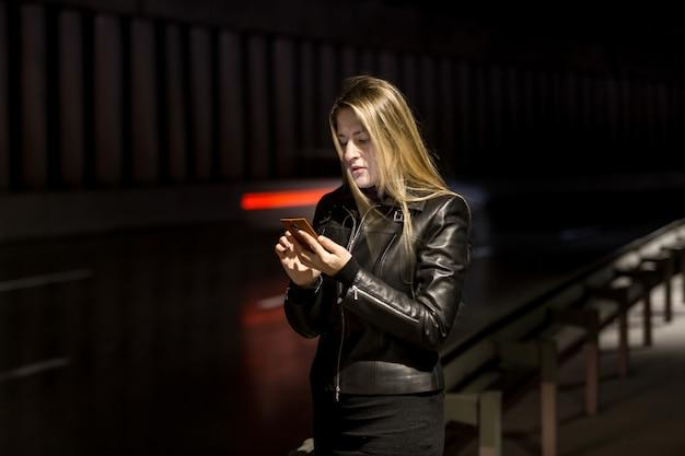 Retrato nocturno de chica rubia mediante teléfono móvil en la calle