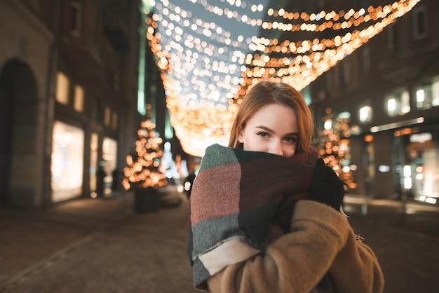 Retrato nocturno de una linda chica de ropa de abrigo en el fondo de la ciudad y las luces del paisaje