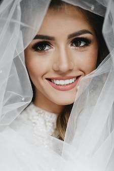Retrato de novia encantadora envuelta en un velo.