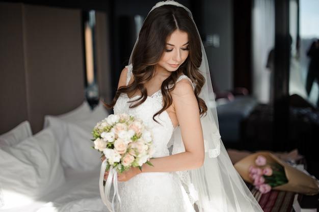 Retrato de novia glamour en elegante vestido de novia, velo y ramo