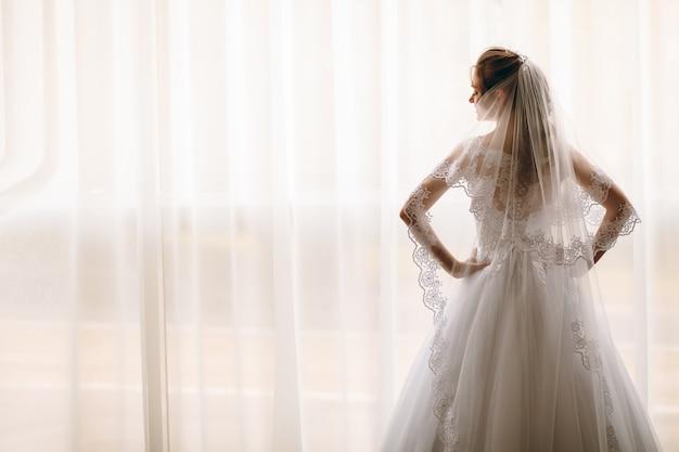 Retrato de novia hermosa en bata de seda blanca con peinado rizado y velo largo de pie cerca de la ventana en el dormitorio
