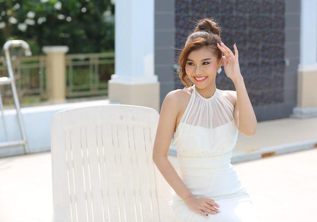 Retrato de novia hermosa en vestido de novia con falda larga y larga sentada junto a la piscina.
