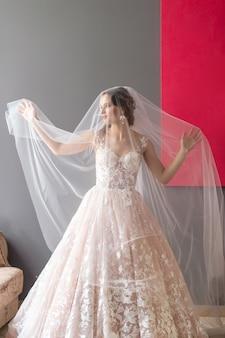 Retrato de novia hermosa en vestido vintage blanco posando bajo velo con imagen roja en la pared