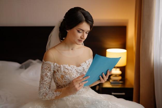 Retrato de novia en la mañana de la boda. hermosa novia con maquillaje y peinado. feliz novia lee un juramento de su futuro esposo