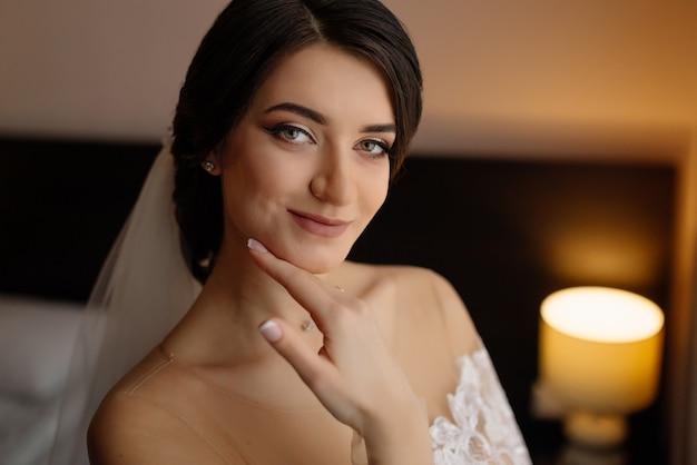 Retrato de novia en la mañana de la boda. hermosa novia con maquillaje y peinado sonriendo.