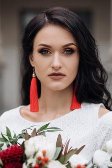 Retrato de novia morena encantadora en vestido blanco con accesorios rojos