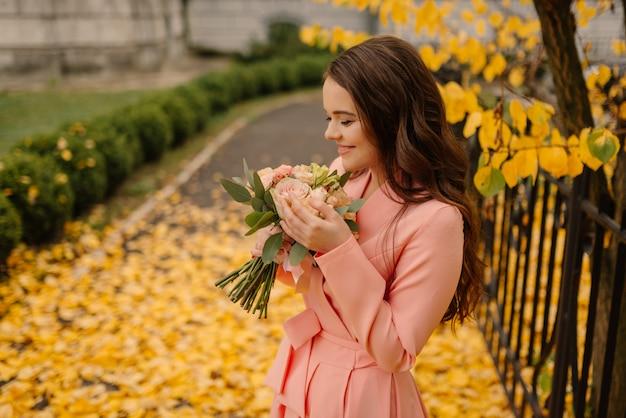 Retrato de la novia morena joven sensual feliz en vestido de novia color de rosa y de pie en el parque de otoño cerca de la catedral vintage y con ramo de boda.