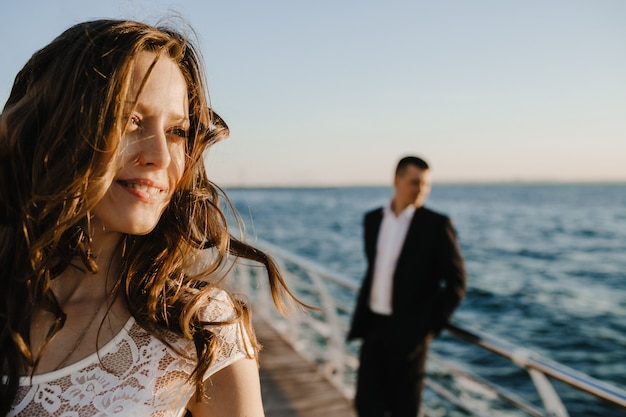 Retrato de una novia morena en primer plano y una silueta de novio en el muelle junto al mar