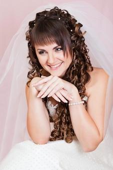 Retrato de novia rubia hermosa con maquillaje en blanco clásico