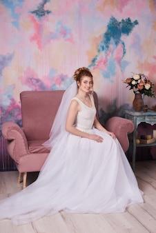 Retrato de novia en velo y joyas en casa en el hermoso gabinete de novia.