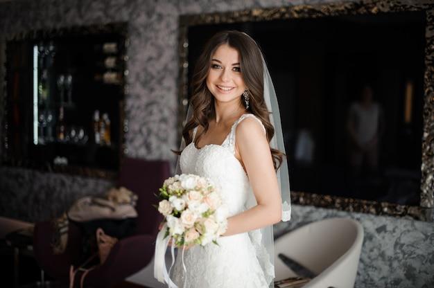 Retrato de novia en vestido de novia blanco y ramo de rosas